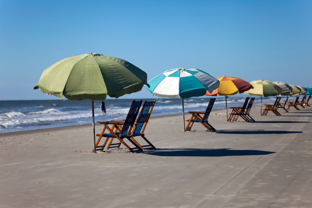 Sun chairs and sun umbrellas on a sandy beach against a clear blue sky in Galveston, Texas